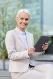 Mulher de negócios de sorriso com PC da tabuleta fora Imagem de Stock