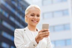 Mulher de negócios de sorriso com smartphone fora Imagens de Stock Royalty Free