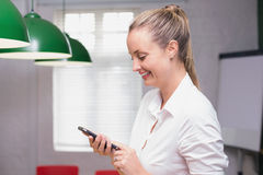Mulher de negócios de sorriso loura que usa o smartphone Imagem de Stock Royalty Free