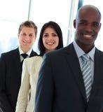 Mulher de negócios de sorriso no foco com sua equipe em a foto de stock