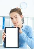 Mulher de negócios de sorriso nova que guarda a tabuleta nas mãos que sentam-se no escritório Foto de Stock Royalty Free