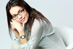 Mulher de negócios de sorriso nova que siiting na cadeira Fotografia de Stock Royalty Free