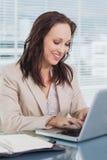 Mulher de negócios de sorriso que datilografa em seu portátil Foto de Stock Royalty Free