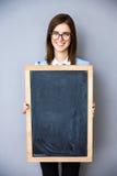 Mulher de negócios de sorriso que está com quadro de avisos Imagem de Stock