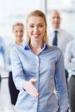 Mulher de negócios de sorriso que faz o aperto de mão no escritório Fotos de Stock Royalty Free