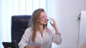 Mulher de negócios de sorriso que guarda uma chave no escritório video estoque