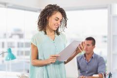 Mulher de negócios de sorriso que lê um caderno Fotos de Stock Royalty Free