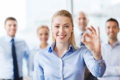 A mulher de negócios de sorriso que mostra está bem assina dentro o escritório Fotografia de Stock Royalty Free