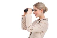 Mulher de negócios de sorriso que olha afastado com binóculos Fotos de Stock Royalty Free