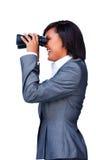 Mulher de negócios de sorriso que olha através dos binóculos Fotografia de Stock