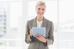 Mulher de negócios de sorriso que olha a câmera e a utilização de sua tabuleta Fotografia de Stock