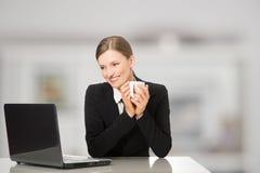 Mulher de negócios de sorriso que senta-se com computador portátil, guardarando a caneca do café e do chá Fotografia de Stock Royalty Free
