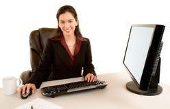 Mulher de negócios de sorriso que senta-se em sua mesa Fotografia de Stock Royalty Free
