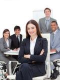 Mulher de negócios de sorriso que senta-se na frente de sua equipe fotos de stock