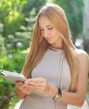 Mulher de negócios de sorriso que usa a tabuleta eletrônica foto de stock royalty free