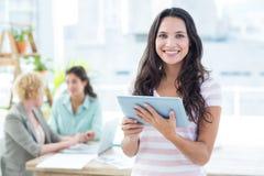 Mulher de negócios de sorriso que usa uma tabuleta com colegas fotos de stock