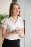 Mulher de negócios de sorriso sonhadora que guarda a tabuleta digital que olha afastado imagens de stock