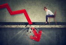 Mulher de negócios deprimida que olha para baixo na seta vermelha de queda que atravessa um assoalho concreto imagens de stock royalty free