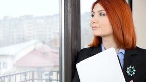 Mulher de negócios do ruivo no vestuário formal que olha fora da janela video estoque
