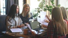 Mulher de negócios dois atrativa que discute o original e que usa um portátil na cafetaria video estoque