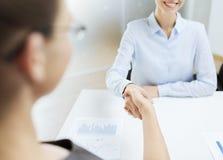 Mulher de negócios dois de sorriso que agita as mãos no escritório Fotografia de Stock Royalty Free