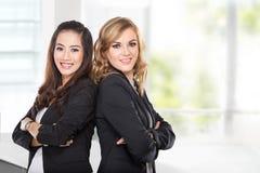 Mulher de negócios dois nova que sorri ao inclinar againts fotos de stock royalty free