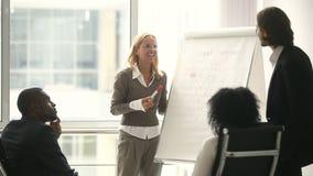 Mulher de negócios e homem de negócios que dão a apresentação usando o flipchart, discutindo a estratégia nova filme