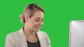 Mulher de negócios elegante que cheering na mesa de escritório que olha o monitor em uma tela verde, chave do croma filme