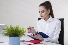Mulher de negócios em uma blusa branca que guarda seu caderno e que lê notas Imagem de Stock