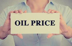 A mulher de negócios entrega guardar o sinal do cartão com mensagem de texto do preço do petróleo Foto de Stock