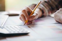 A mulher de negócios entrega a pena de terra arrendada que trabalha com a calculadora para calcula o negócio do retorno dos lucro fotografia de stock royalty free