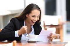 Mulher de negócios entusiasmado que lê uma letra fora foto de stock