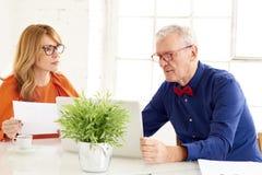Mulher de negócios envelhecida média e homem de negócio superior que trabalham junto no portátil no escritório fotos de stock