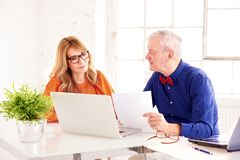 Mulher de negócios envelhecida média e homem de negócio superior que trabalham junto no portátil no escritório foto de stock royalty free
