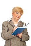 A mulher de negócios envelhecida média escreve na agenda imagens de stock