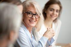 Mulher de negócios envelhecida de sorriso que olha de escuta o colega no chá foto de stock