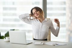 Mulher de negócios esgotada que toma a ruptura do estiramento sedentariamente do trabalho fotos de stock