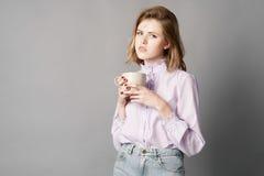 A mulher de negócios está e guarda uma caneca em sua mão Fotografia do estúdio Um em um fundo cinzento Imagens de Stock