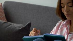 Mulher de negócios está meditando enquanto está sentada em um sofá e escrevendo ideias video estoque