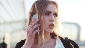 A mulher de negócios europeia ocupada atrativa fala em seu telefone, verifica o tempo, e toca em seu cabelo Equipamento formal oc video estoque