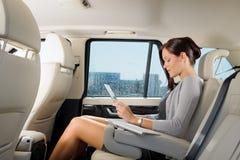 Mulher de negócios executiva na tabuleta de toque do trabalho do carro Foto de Stock
