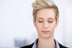 Mulher de negócios With Eyes Closed no escritório imagens de stock royalty free