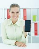 Mulher de negócios fêmea nova que mostra o smartphone à disposição que senta-se no escritório Imagem de Stock