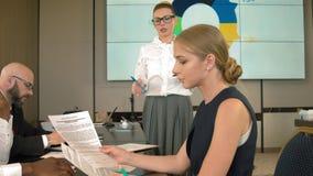 A mulher de negócios fala aos colegas com um relatório em projetos principais filme