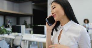 A mulher de negócios faz a chamada de telefone celular bem sucedida o suporte de sorriso feliz no escritório criativo que fala so filme
