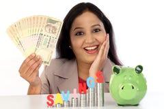 Mulher de negócios feliz com a pilha de moedas e de guardar notas da rupia Imagem de Stock Royalty Free