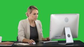 Mulher de negócios feliz elegante que trabalha no computador em uma tela verde, chave do croma filme