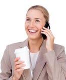 Mulher de negócios feliz no telefone ao beber Fotos de Stock