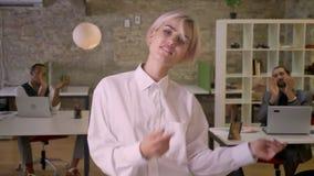 A mulher de negócios feliz nova está dançando no escritório, colegas está aplaudindo, trabalha o conceito, relaxa o conceito filme