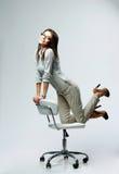 Mulher de negócios feliz nova que tem o divertimento na cadeira do escritório imagem de stock royalty free